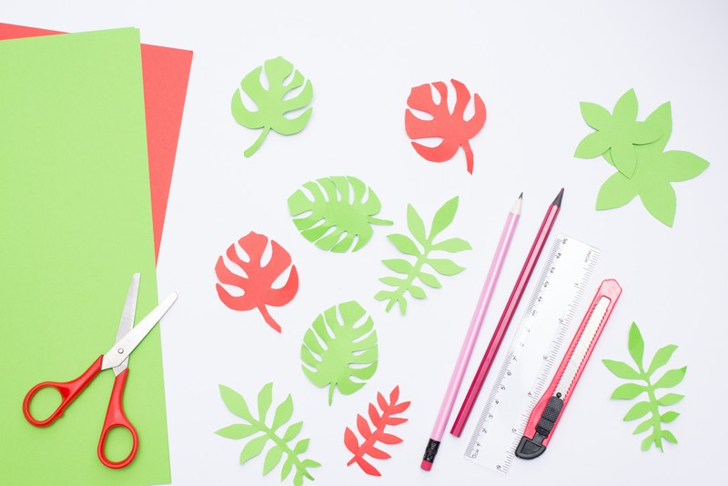Creating paper tropic leaves on white table. Easy kids crafts idea. Top view